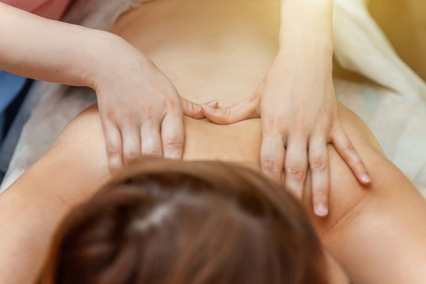 Woman getting body back massage treatment in spa salon
